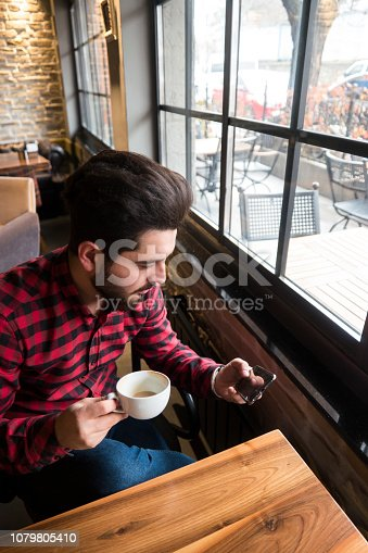 824167622istockphoto Happy hipster man at coffee shop texting on mobile phone 1079805410