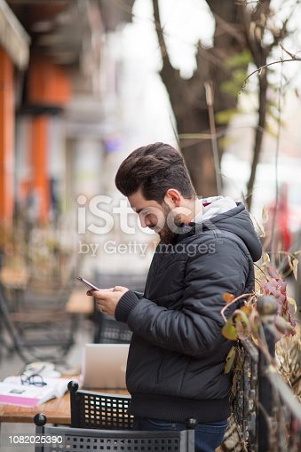 824167622istockphoto Happy hipster man at coffee shop texting on mobile phone 1082025390