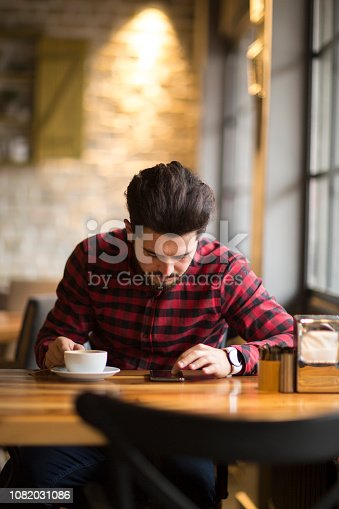 824167622istockphoto Happy hipster man at coffee shop texting on mobile phone 1082031086