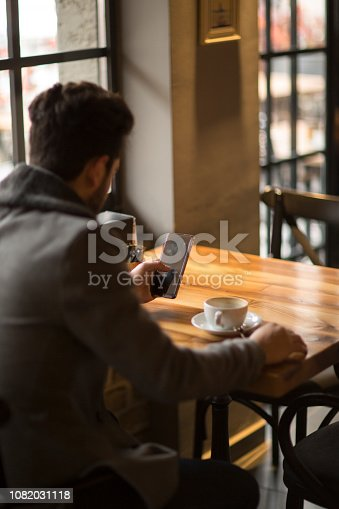 824167622istockphoto Happy hipster man at coffee shop texting on mobile phone 1082031118