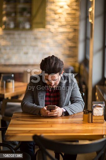824167622istockphoto Happy hipster man at coffee shop texting on mobile phone 1082031380