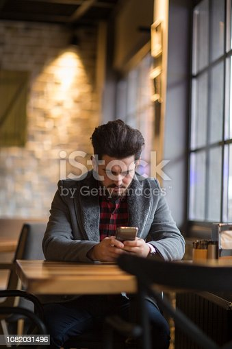 824167622istockphoto Happy hipster man at coffee shop texting on mobile phone 1082031496
