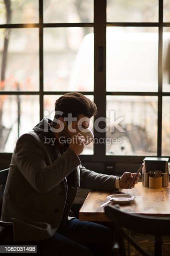 824167622istockphoto Happy hipster man at coffee shop texting on mobile phone 1082031498