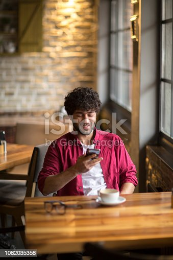 824167622istockphoto Happy hipster man at coffee shop texting on mobile phone 1082035358