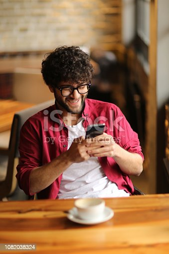 824167622istockphoto Happy hipster man at coffee shop texting on mobile phone 1082038324