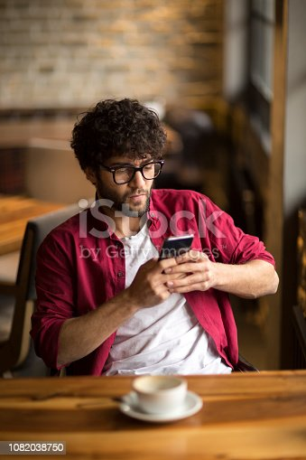 824167622istockphoto Happy hipster man at coffee shop texting on mobile phone 1082038750