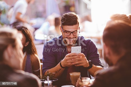 Young man drinking coffee with friends at café and checking his social networks on smartphone