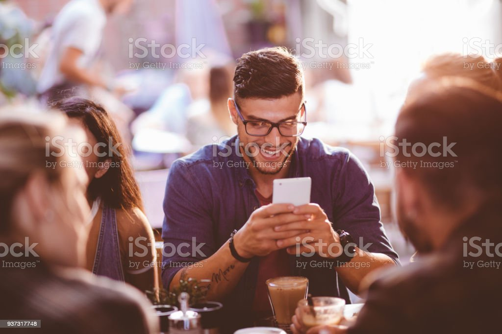 Happy hipster man at coffee shop texting on mobile phone stock photo
