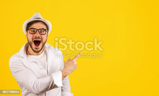 istock Happy hipster pointing up on yellow 952768944
