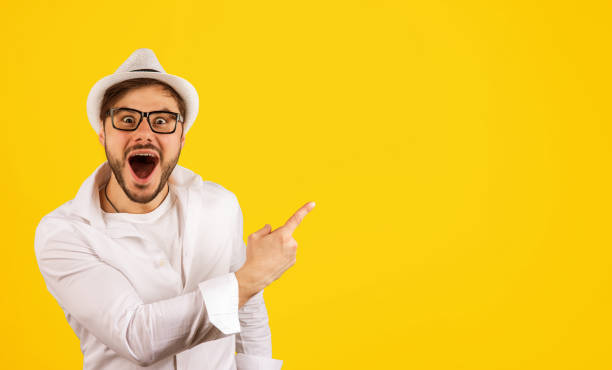Happy hipster pointing up on yellow stock photo