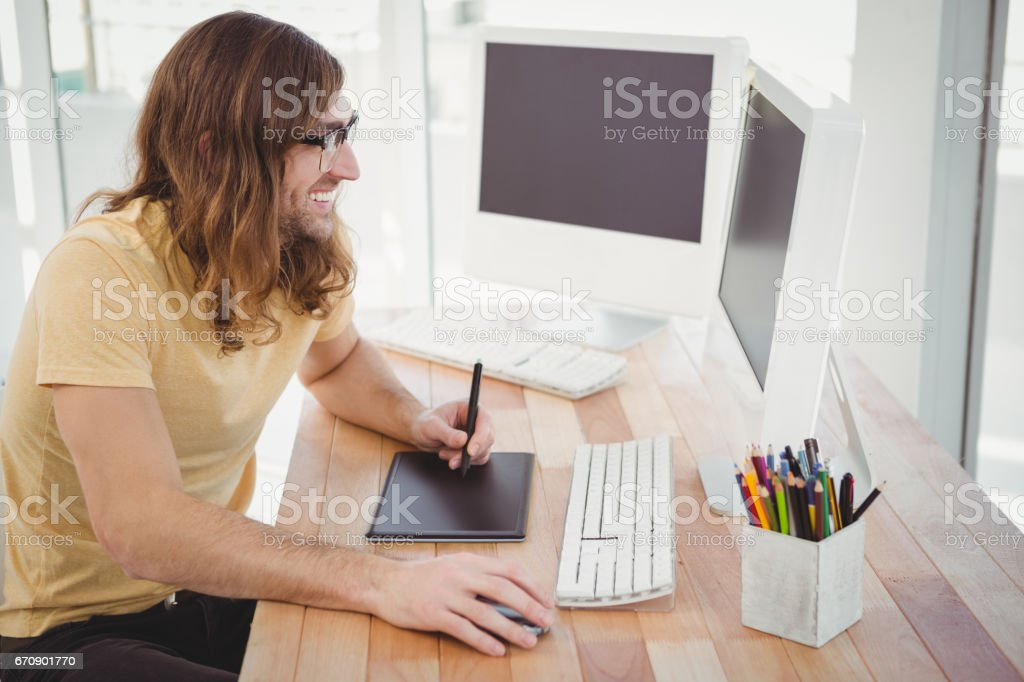 Happy hipster with graphics tablet looking at computer stock photo