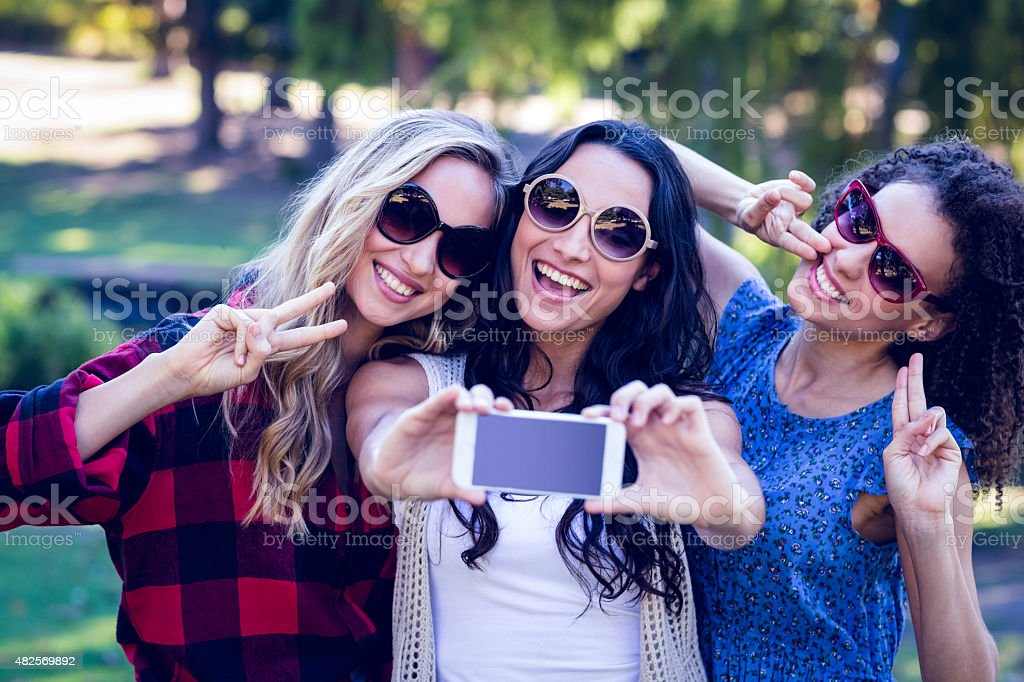 Happy hipsters taking a selfie in the park stock photo