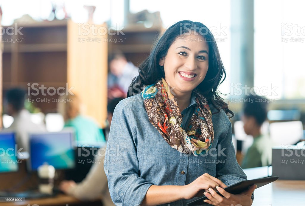 Happy Hispanic adult woman using digital tablet in college library stock photo