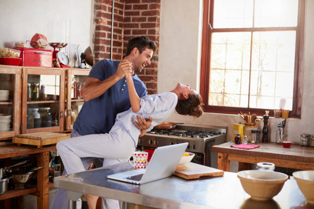 happy hispanic couple dancing in kitchen in the morning - coppia felice foto e immagini stock