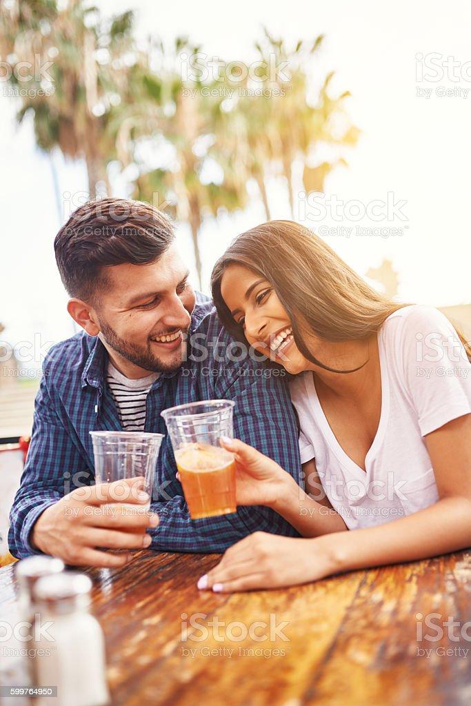 happy hispanic couple drinking beer in outdoor pub stock photo