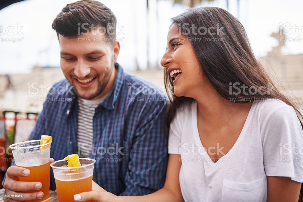 happy hispanic couple drinking beer in outdoor pub stock photo