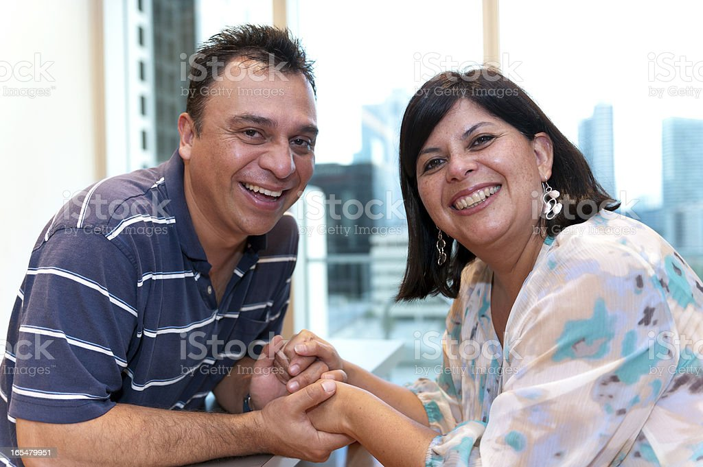 Happy Hispanic couple holding hands and laughing royalty-free stock photo