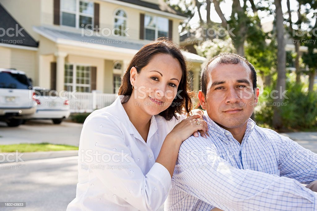 Happy Hispanic couple sitting with house in background royalty-free stock photo