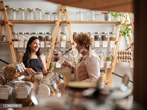 Happy hispanic employee and senior female customer standing next to the shelves of a sustainable shop and smiling at each other.
