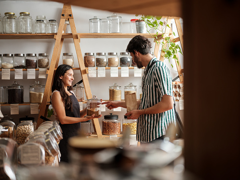 A happy hispanic employee helping a young man in a zero waste store.