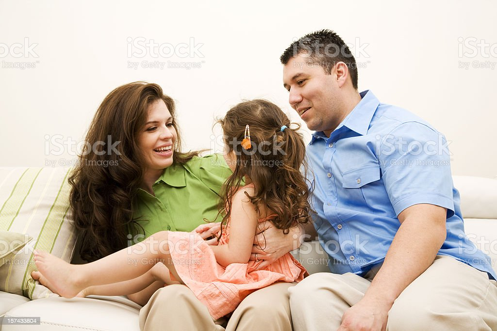Happy Hispanic Family at Home sitting on the couch together royalty-free stock photo