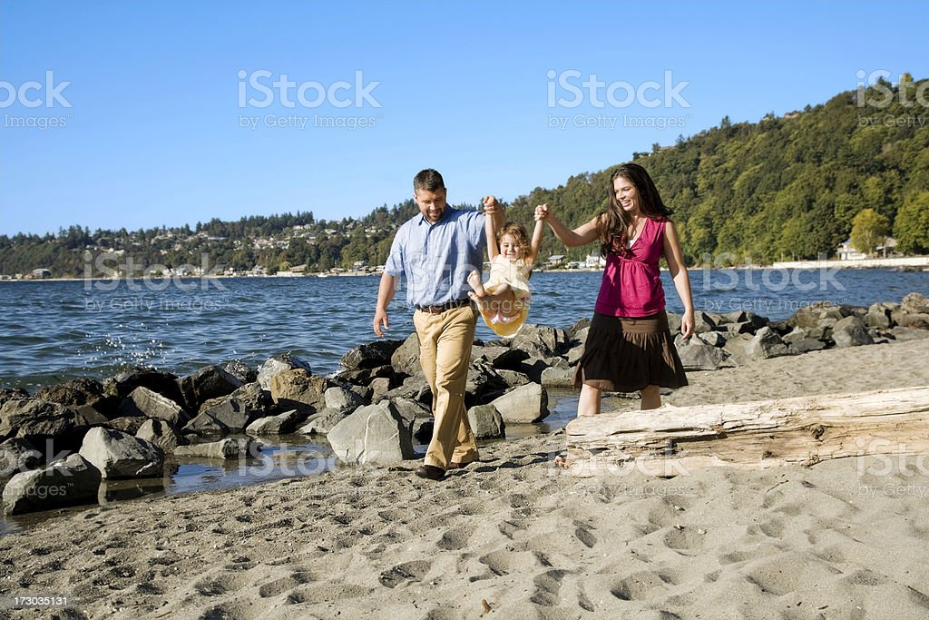 Happy Hispanic Family playing ocean beach sand mother father daughter stock photo