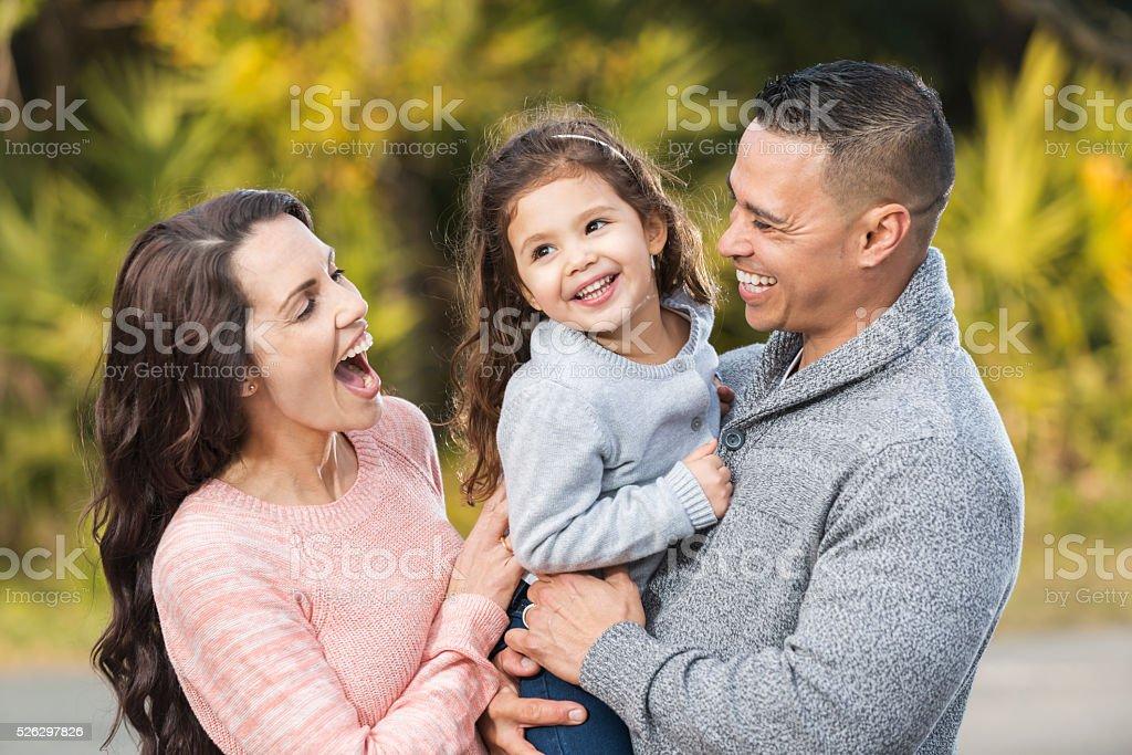 Happy Hispanic family with little girl stock photo