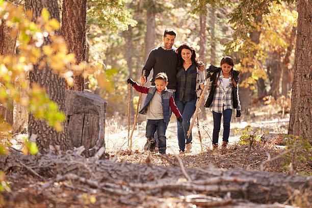 feliz familia hispana con dos niños caminando en un bosque - excursionismo fotografías e imágenes de stock