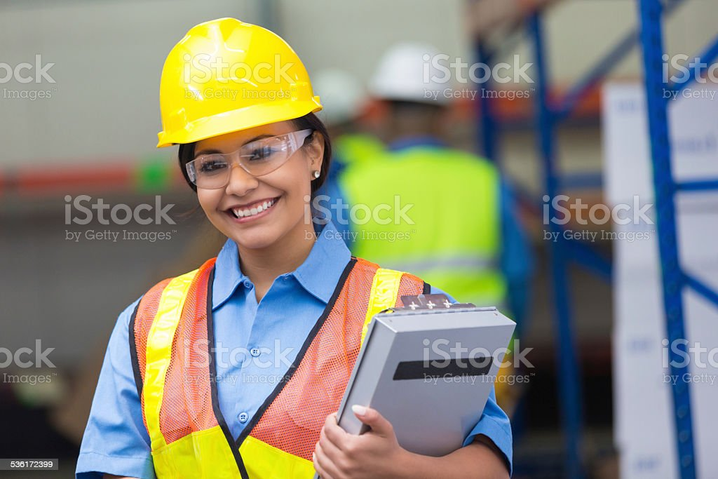 Happy Hispanic female blue collar worker in warehouse stock photo