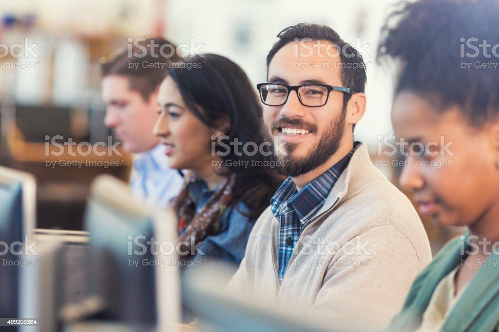 hipster homem hispânico feliz usando o computador classe comptuer da faculdade - foto de acervo