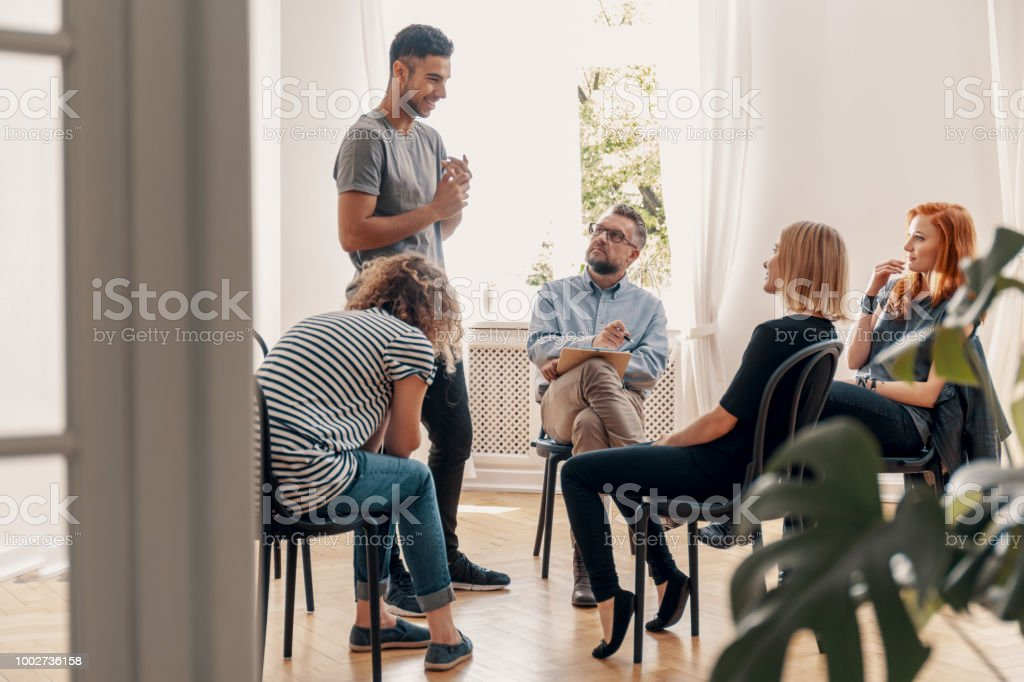 Happy hispanic man talking to his support group about his successful fight with drug addiction stock photo