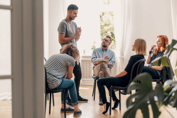 Happy hispanic man talking to his support group about his successful fight with drug addiction Happy hispanic man talking to his support group about his successful fight with drug addiction dependency stock pictures, royalty-free photos & images