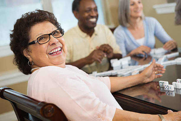 happy hispanic senior woman playing dominoes with friends - game of life stock photos and pictures