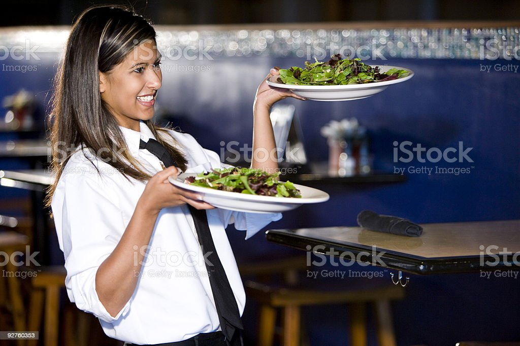Happy hispanic waitress serving salads royalty-free stock photo