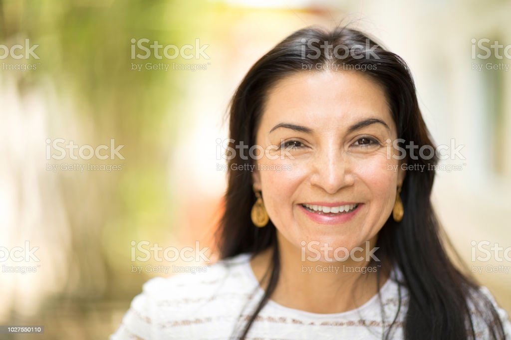 Happy Hispnaic woman smiling and standing outside. royalty-free stock photo