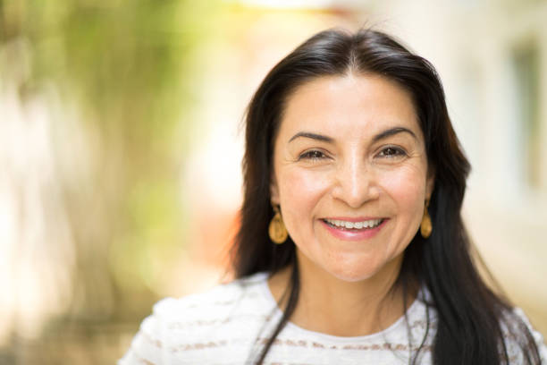 Happy Hispnaic woman smiling and standing outside. Portrait of a happy Hispnaic woman smiling. latin american and hispanic ethnicity stock pictures, royalty-free photos & images
