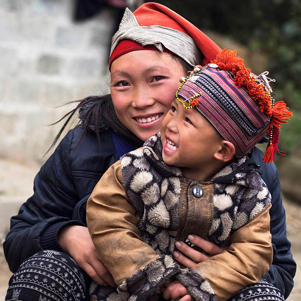 Happy Hmong Hill Tribe Woman and Child, Sapa, Vietnam Happy Hmong woman and child smiling, sitting outside their house at Giang Ta Chai village near the hill town of Sa Pa, Lao Cai Province, North Vietnam. vietnamese ethnicity stock pictures, royalty-free photos & images