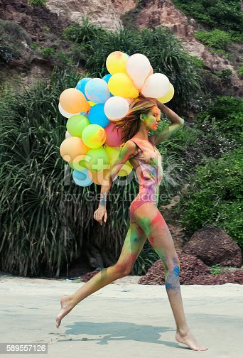 Young slender girl celebrates Indian festival of Holi on the ocean with colorful balloons.