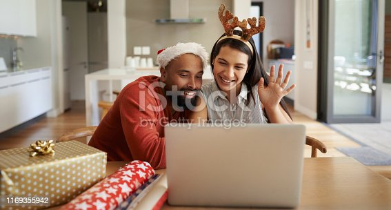 Shot of a happy young couple using a laptop during the Christmas holidays at home