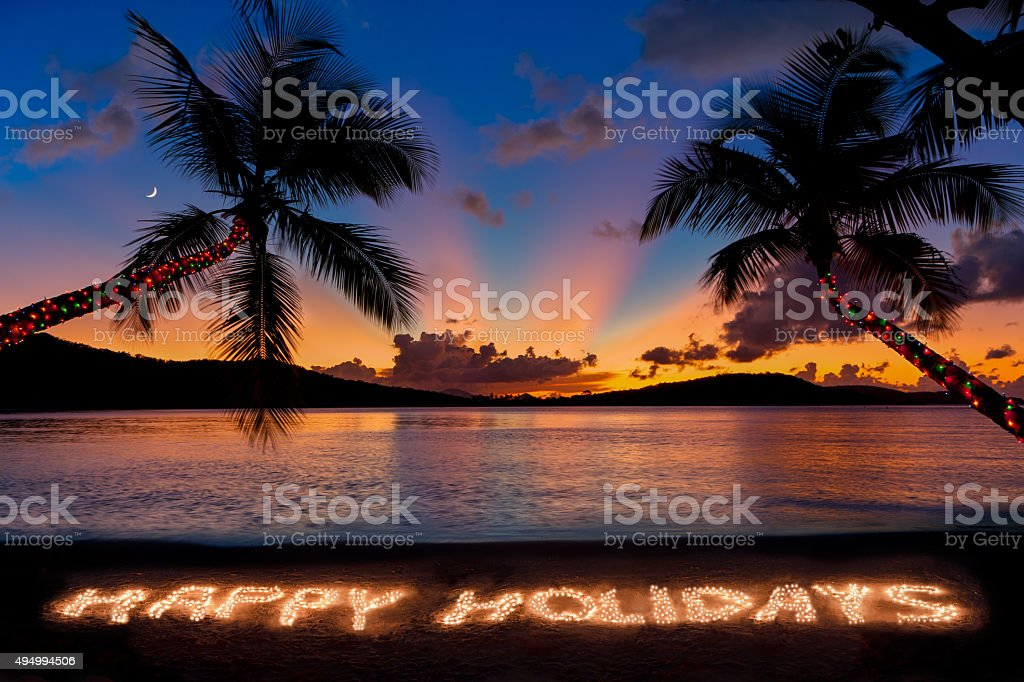 Happy Holidays made with Christmas lights at a tropical beach stock photo