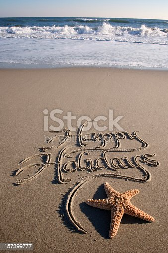 Happy Holidays message handwritten in the sand with a starfish and crashing waves in the background
