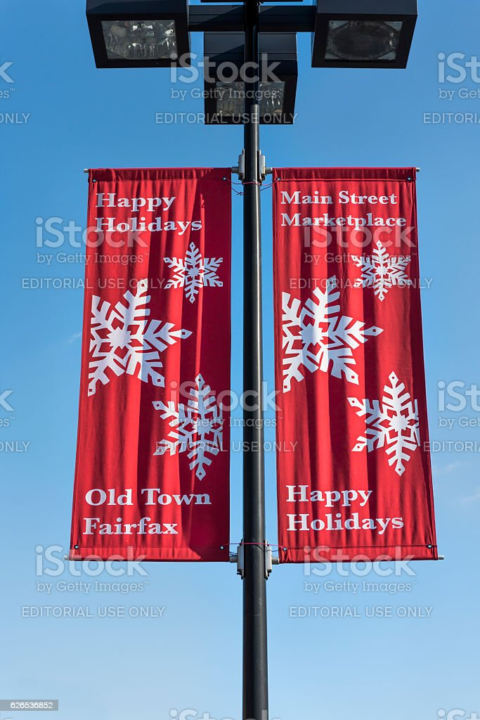 Happy holidays red banner on lamp post in downtown stock photo