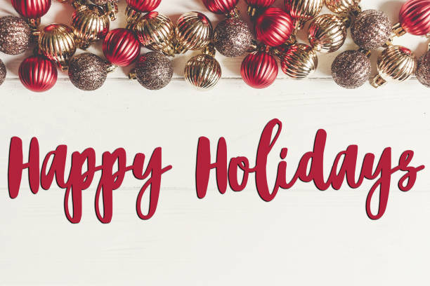 happy holidays text, seasonal greetings card sign. christmas flat lay. red and gold christmas ornaments  frame or border on white wooden background top view with stock photo