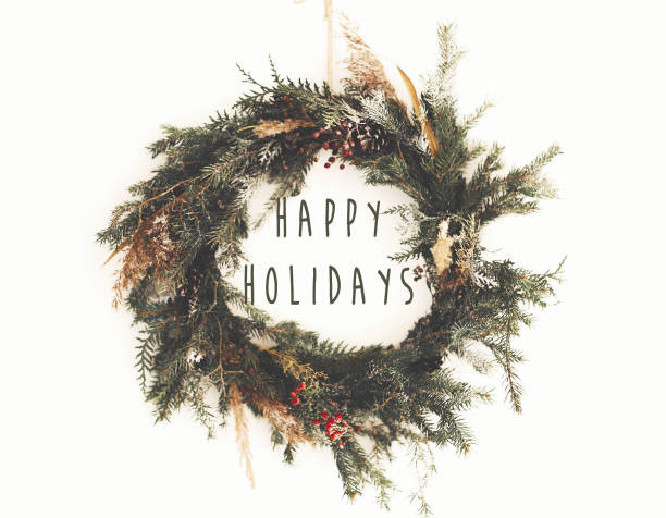 happy holidays text sign on  christmas rustic wreath. creative rural  wreath with fir branches, berries, pine cones, herbs hanging on white wall in room. seasons greeting card - happy holidays stock pictures, royalty-free photos & images