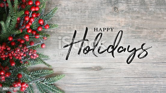 istock Happy Holidays Text with Holiday Evergreen Branches and Berries Over Rustic Wooden Background 880147466