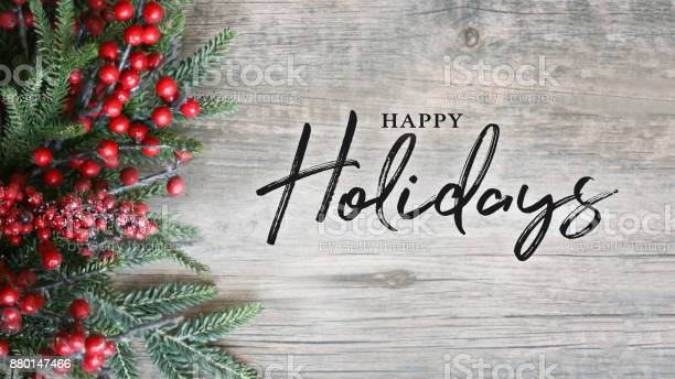 Happy holidays text with holiday evergreen branches and berries over picture id880147466?b=1&k=6&m=880147466&s=612x612&h=uyxjv2hlnucnioeopvsqism7n vqj 2yuy7qepef5m8=
