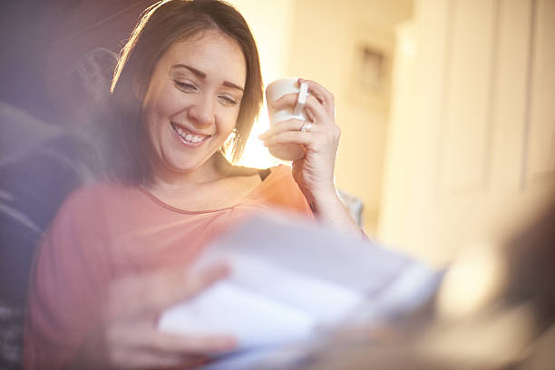 happy home finances happy young woman sat on the sofa in her living room smiling at her latest bank statement relief emotion stock pictures, royalty-free photos & images