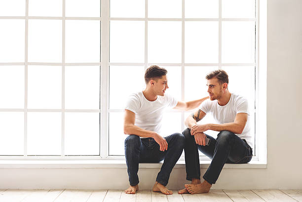 happy homosexual couple resting on windowsill - freundin tattoos stock-fotos und bilder