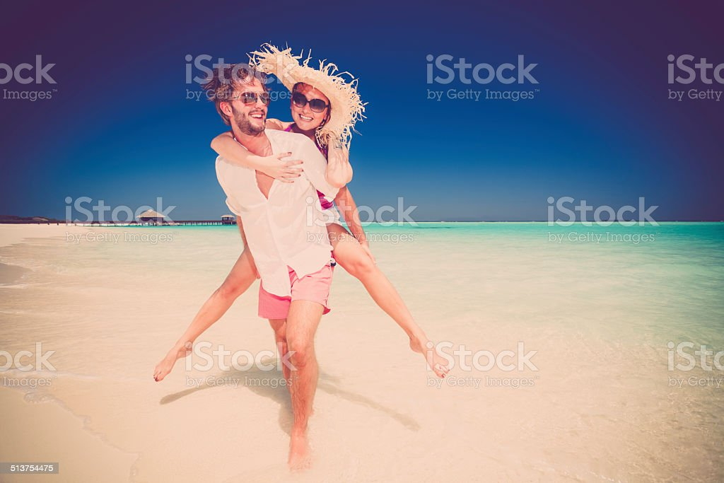 happy honeymoon couple on sandy beach stock photo