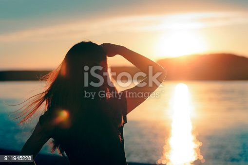 Silhouette of a dreamer girl looking hopeful at the horizon